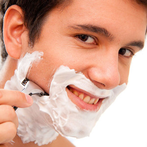 Man shaves with a razor blade and shaving cream